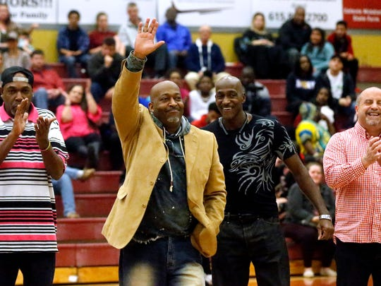 Leon Corder (left) and his brother, Tim, acknowledge the crowd as the 1985-86 Riverdale boys basketball team is recognized Friday.