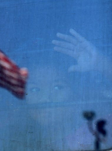 A migrant child looks out the window of a bus as protesters