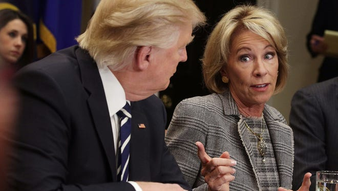 U.S. Secretary of Education Betsy DeVos (R) speaks as President Donald Trump listens during a parent-teacher conference listening session at the Roosevelt Room of the White House February 14, 2017 in Washington, DC. The White House held the session to discuss education.
