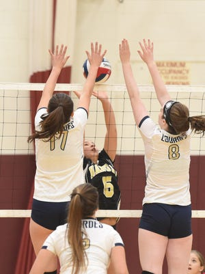 Nanuet's Laura Zazyczny, center, tries to get the keep the ball over the net as Lourdes' Jessica D'Auria, left, and Anna Kolosky, right, block during Tuesday's game.