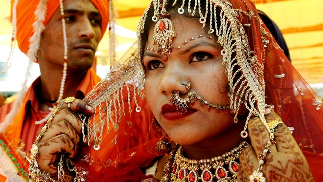 An Indian bride sits with her groom during a mass marriage ceremony for some 125 poverty-stricken couples from the India-Pakistan border areas, at Gurdwara Baba Jallan Dass in the village of Naushehra Dhala on April 15, 2010 .