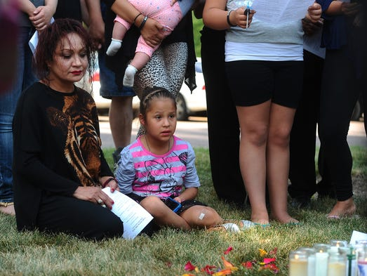 Beverly Guerra's aunt Laura Rodriguez and Guerra's daughter, Isabell Figueroa, 7, gather with family members and supporters during a vigil at 22nd Street and Cleveland Avenue in Sioux Falls on Wednesday, July 16, 2014.
