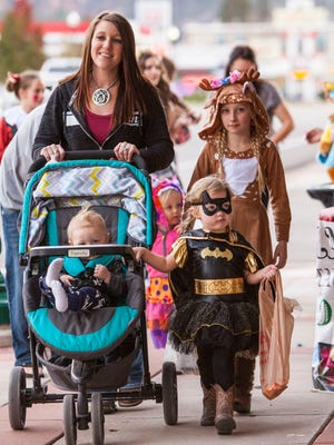 Families dressed in costumes walk along Main Street in Cedar City for the Hocus Focus trick-or-treating event, Saturday, Oct. 29, 2016.