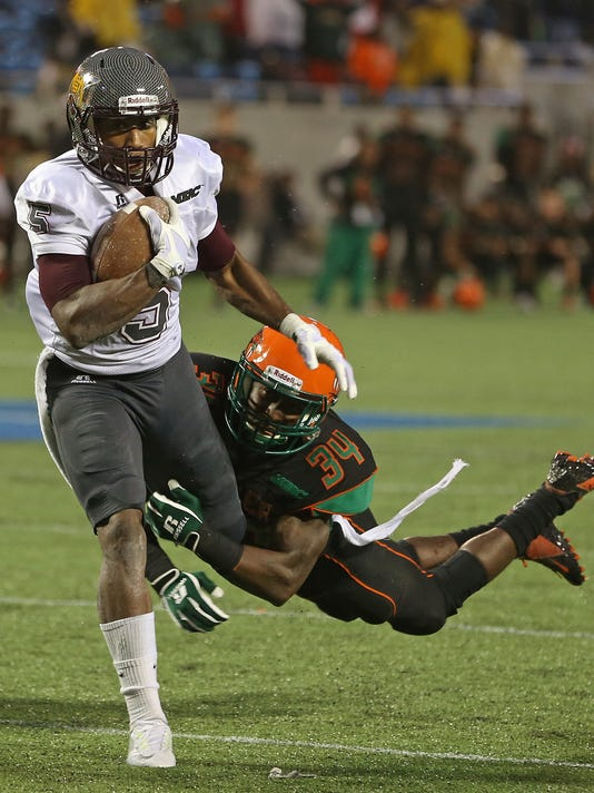 Bethune-Cookman's Jhomo Gordon (5) breaks the attempted tackle of Florida A&M's John Boston (34) to score a touchdown in overtime at the Florida Classic in Orlando, Fla,, Saturday, Nov. 22, 2014. Bethune-Cookman won 18-17 in overtime. (AP Photo/Daytona Beach News-Journal, Nigel Cook)
