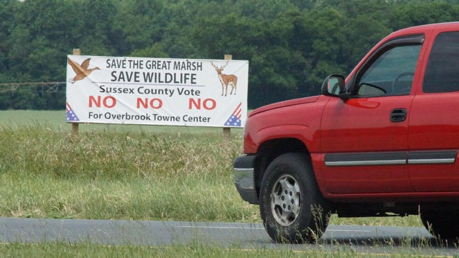 A driver passes a sign, in 2015, at Cave Neck Road and Del. 1 opposing the Overbrook Town Center, a proposed shopping complex north of Lewes.