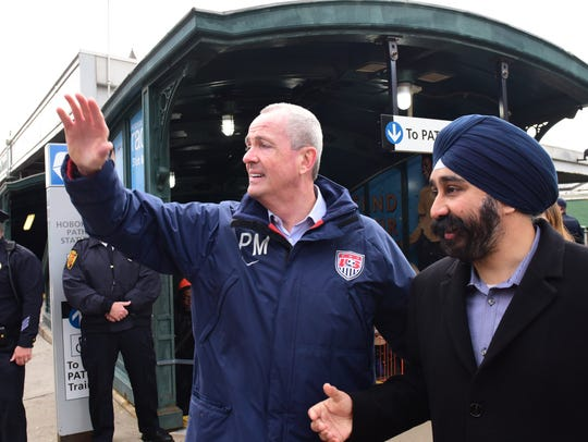 Phil Murphy, left, New Jersey governor-elect, greets commuters at the Hoboken PATH Station on Wednesday morning with Ravi Bhalla, Hoboken mayor-elect.