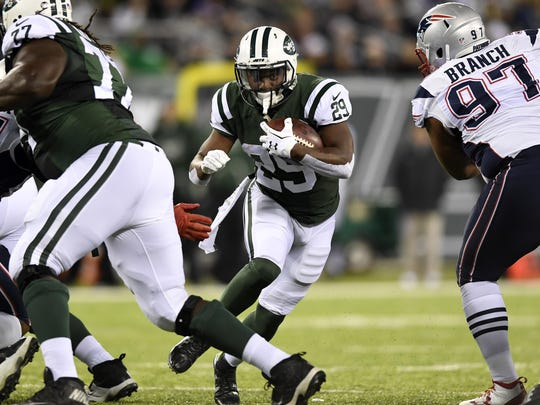 Jets running back Bilal Powell carries the ball through a gap in the line in Sunday's game against the Patriots.