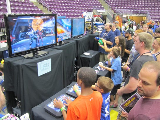 A crowd of people try their hand at video games Saturday
