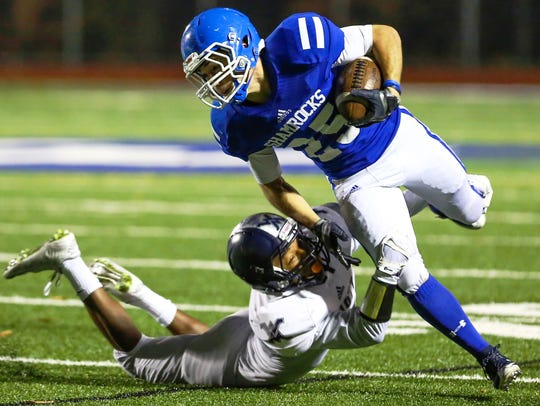 Catholic Central's Nicholas Capatina (top) keeps his