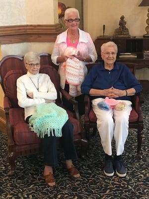 Delores Fangman is sitting holding the green quilt. Pauline Eimen is sitting holding the hats, while Evelyn Langlas is standing.