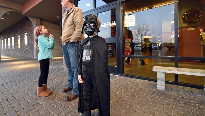 John Mason Evans, 6, dressed as Darth Vader, waits with his family outside Malco Grandview in Madison Thursday evening before heading into the premier of Star Wars: The Force Awakens.