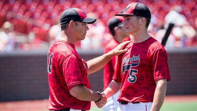 Wapahani assistant Jason Dudley talks to Alec Summers during the Raiders' 9-2 semistate win over Hebron at Municipal Stadium in Kokomo Saturday, June 10, 2017.