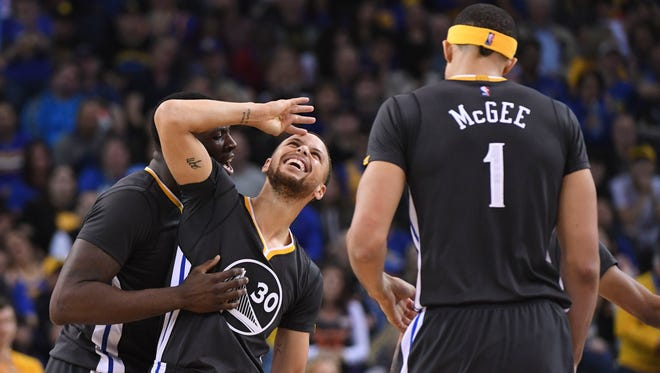 Stephen Curry reacts with teammates Draymond Green (left) and JaVale McGee (right).