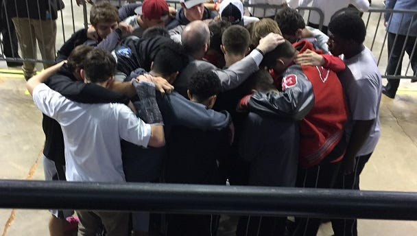 Members of the Belle Chasse wrestling team huddle in prayer on the floor of the CenturyLink Center in supponf teammate Jovany Cortes, who passed away Feb. 2.