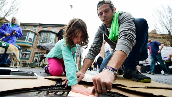 "Caleb Robertson of York, right, helps 5-year-old Katelyn Moyer of York Township make a print of the letter ""K"" from a manhole cover on Beaver Street at Go Green in the City in York Saturday, April 22, 2017. Robertson called the project Beaver Street Press."