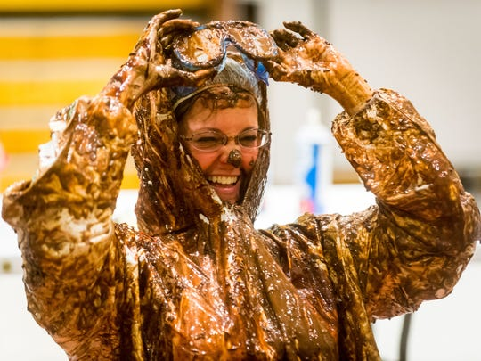 """Snow Hill Elementary principal Dr. Mary Anne Cooper receives the """"human sundae"""" treatment from students as part of a reward for raising the most money during a program called One School, One Book at Snow Hill Elementary on Monday, May 2."""