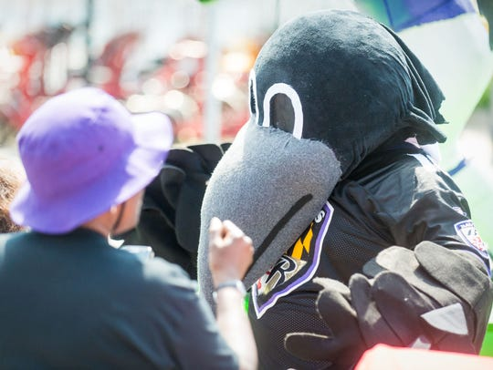 Baltimore Ravens mascots wave to fans on Baltimore