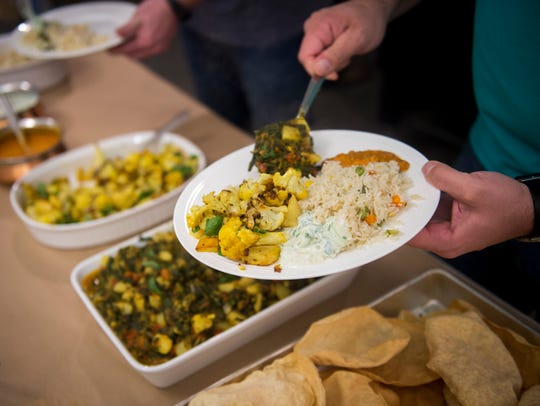 Guests fill their plates with vegetarian dishes made