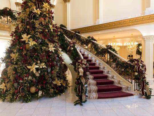 The large Christmas tree, decorated by Samuel Franklin Floral Design, stands next to the grand staircase in the foyer at Villa Collina.
