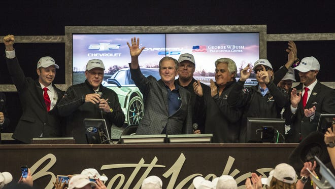 Former President George W. Bush waves to crowd during his appearance at the Barrett-Jackson Auction in Scottsdale on Jan. 20, 2018. He signed the car that was sold for $1.4 million which will be donated to veterans.