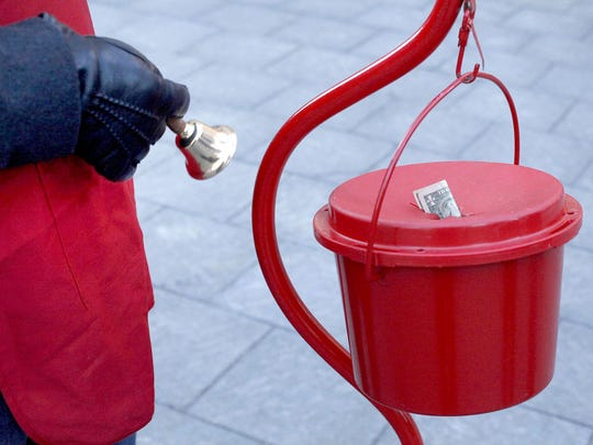 A volunteer rings the bell to collect donations for the Salvation Army Red Kettle fundraising campaign.