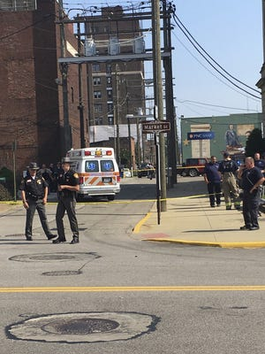 Steubenville, Ohio, police officers, Jefferson County Sheriff's Department deputies and other investigators work following an ambush-style shooting of Jefferson County Judge Joseph Bruzzese Jr. on Monday, Aug. 21, 2017, on the Court Street side of the Jefferson County Courthouse in Steubenville, Ohio. Bruzzese was shot and wounded Monday morning as he walked toward his county's courthouse, and a suspect was killed after a probation officer returned fire, officials said. (Mark Law/Herald-Star via AP)