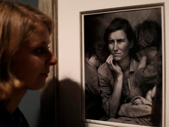 "A Tate member of staff poses next to American photographer Dorothea Lange's ""Migrant Mother"", from 1936, at the press view of ""The Radical Eye: Modernist Photography from the Sir Elton John Collection"" exhibition at the Tate Modern gallery in London, Tuesday, Nov. 8, 2016. British musician Elton John's collection of international modernist photography from the 1920s to 50s includes almost 200 prints and opens to the public on November 10."