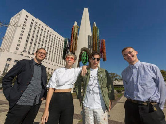 "In this Wednesday, Feb. 1, 2017, photo members of the Triforium project, from left, Tanner Blackman, Claire Evans, Jona Bechtolt and Tom Carroll,  pose for a photo with Joseph L. Young's Triforium a ""polyphonoptic"" public sculpture at the Fletcher Bowron Square downtown Los Angeles.  For 40 years Joseph Young festooned public buildings, open spaces and private places across his adopted city of Los Angeles with dozens of brilliant, larger-than-life artworks.  Mocked for 42 years as pointless and silly looking, the six-story, space-age-like structure may finally get a second chance, thanks to a $100,000 innovation grant."