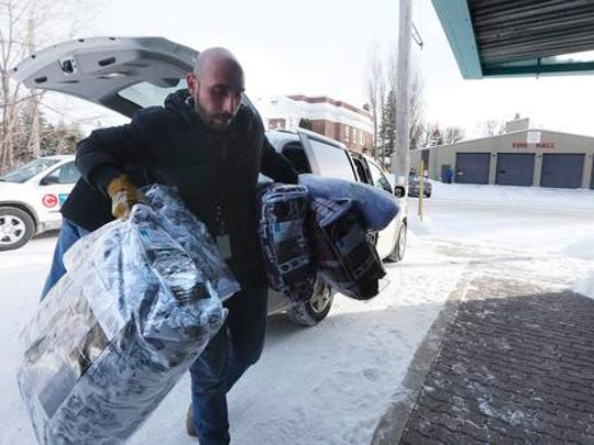 Fadel Alshawwa, Manitoba Interfaith Immigration Council, brings blankets into a community hall for refugees that may walk across the border in Emerson, Manitoba, Thursday, Feb. 9, 2016. Refugees have been crossing into Canada at Emerson and authorities had a town hall meeting in Emerson to discuss their options.