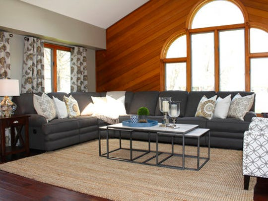 This undated photo provided by Leedy Interiors shows a New Jersey home where interior designer Sarah Dooley helped this baby boomer client incorporate a sectional with reclining pieces into a room that combines comfort and style. As baby boomers age and downsize, they are demanding furniture that's functional and comfortable.