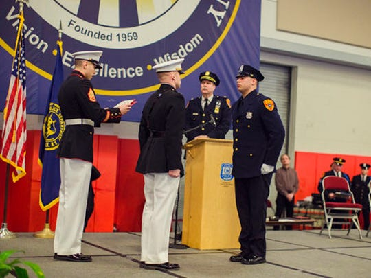Matias Ferreira, center, receives his diploma during his graduation from the Suffolk County Police Department Academy at the Health, Sports and Education Center in Suffolk, Long Island, New York, Friday, March 24, 2017. Ferreira, a former U.S. Marine Corps lance corporal who lost his legs below the knee when he stepped on a hidden explosive in Afghanistan in 2011, is joining a suburban New York police department. The 28-year-old graduated Friday from the Suffolk County Police Academy on Long Island following 29 weeks of training.