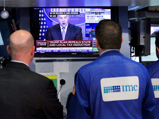 Specialists on the floor of the New York Stock Exchange watch Gary Cohn, director of the White House National Economic Council, Wednesday, April 26, 2017. President Donald Trump proposed dramatic cuts in the taxes paid by corporations big and small Wednesday in an overhaul his administration says will spur economic growth and bring jobs and prosperity to America's middle class.