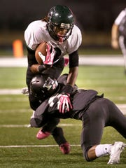 Cordova wide receiver Edward Johnson is stopped by Houston's Jeramie Tate during their game at Houston High School.