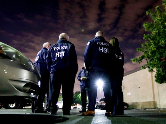 U.S. Immigration and Customs Enforcement agents gather before serving a employment audit notice at a 7-Eleven convenience store Wednesday, Jan. 10, 2018, in Los Angeles. Agents said they targeted about 100 7-Eleven stores nationwide Wednesday to open employment audits and interview workers.