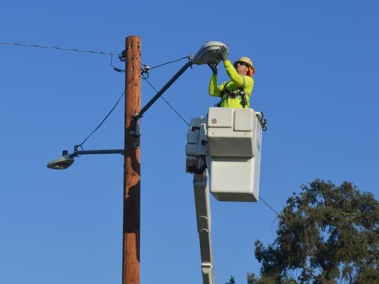 Nathan Alexander, a journeyman lineman, installs LED lights on a pole on Watson Street in Visalia.