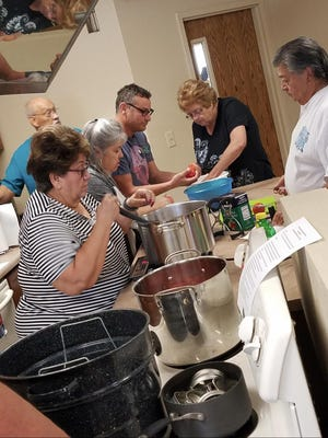 Pueblo County residents learn how to preserve tomatoes during a hands-on water bath canning class.  This class is part of an annual series on food preservation offered by CSU Extension Pueblo County.