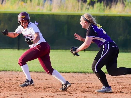 Ankeny's Kennedy Thomas (25) gets chased by Indianola first baseman Abby Gehringer (24) in a squeeze play on Tuesday, June 12, 2016, during the Regional Finals softball game between Ankeny and Indianola at Ankeny High School.