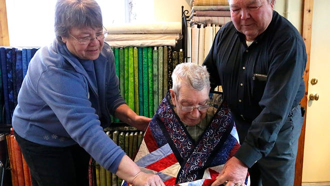 Cheryl Meyer and Jim Simons of Quilter's Rule wrap a patriotic quilt around 98-year-old World War II veteran Roy Meyer, who was a Yeoman Second Class in the U.S. Navy. The quilt was made by Roy's son, Gerry Meyer.