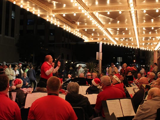 Joe Stephens directs the Abilene Community Band during its performance outside the Paramount Theatre during City Sidewalks. The band will be inside the downtown Abilene theater Tuesday for its holiday show.
