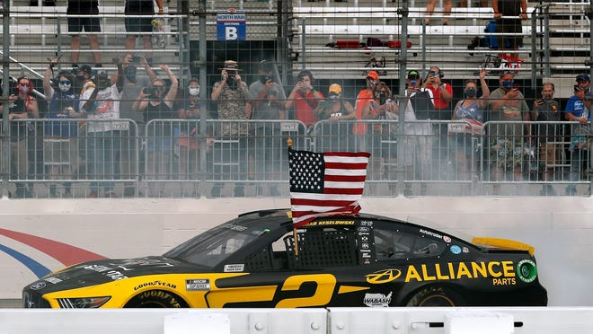 Driver Brad Keselowski celebrates with a burnout and the American flag after winning during a NASCAR Cup Series auto race, Sunday, Aug. 2, 2020, at the New Hampshire Motor Speedway in Loudon, N.H.