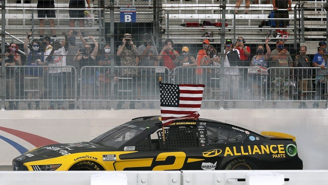 Brad Keselowski celebrates with a burnout and the American flag after winning on Sunday in New Hampshire.