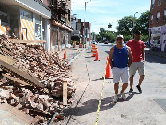 From left, Fernando Hernandez and Robert Vellos, former residents at 17 Academy St., survey the demolished building on Tuesday.
