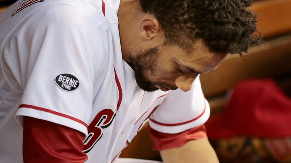 Reds center fielder Billy Hamilton hangs his head in the dugout as he's checked on by the training staff before leaving Tuesday's game in the top of the fourth inning.