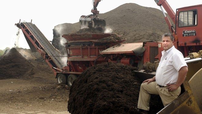 Evans Landscaping owner Doug Evans stands on some black mulch from a front loader's bucket near one of the company's mulch hoppers at its mulch production facility in Newtown April 30, 2003.
