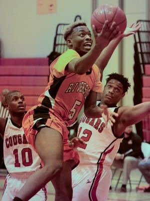 Riverside's Carlos Curtis drives past  Eric Walker (left) and Damiga Bunn in the final overtime.