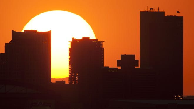 The sun dips behind the skyline of downtown Phoenix, Ariz. This picture was taken on the hottest day of the summer so far with a high of 115 degrees on June 27, 2011.