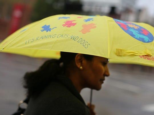 Sarah Emnut, of the West End, walks in the rain in downtown Cincinnati.