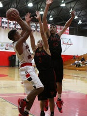 Palm Springs' Ricky Wright shoots the ball while being defended by Vista's Taurus Samuels, center, and Davin Lemon-Rodriquez on Saturday. Vista won 60-48.