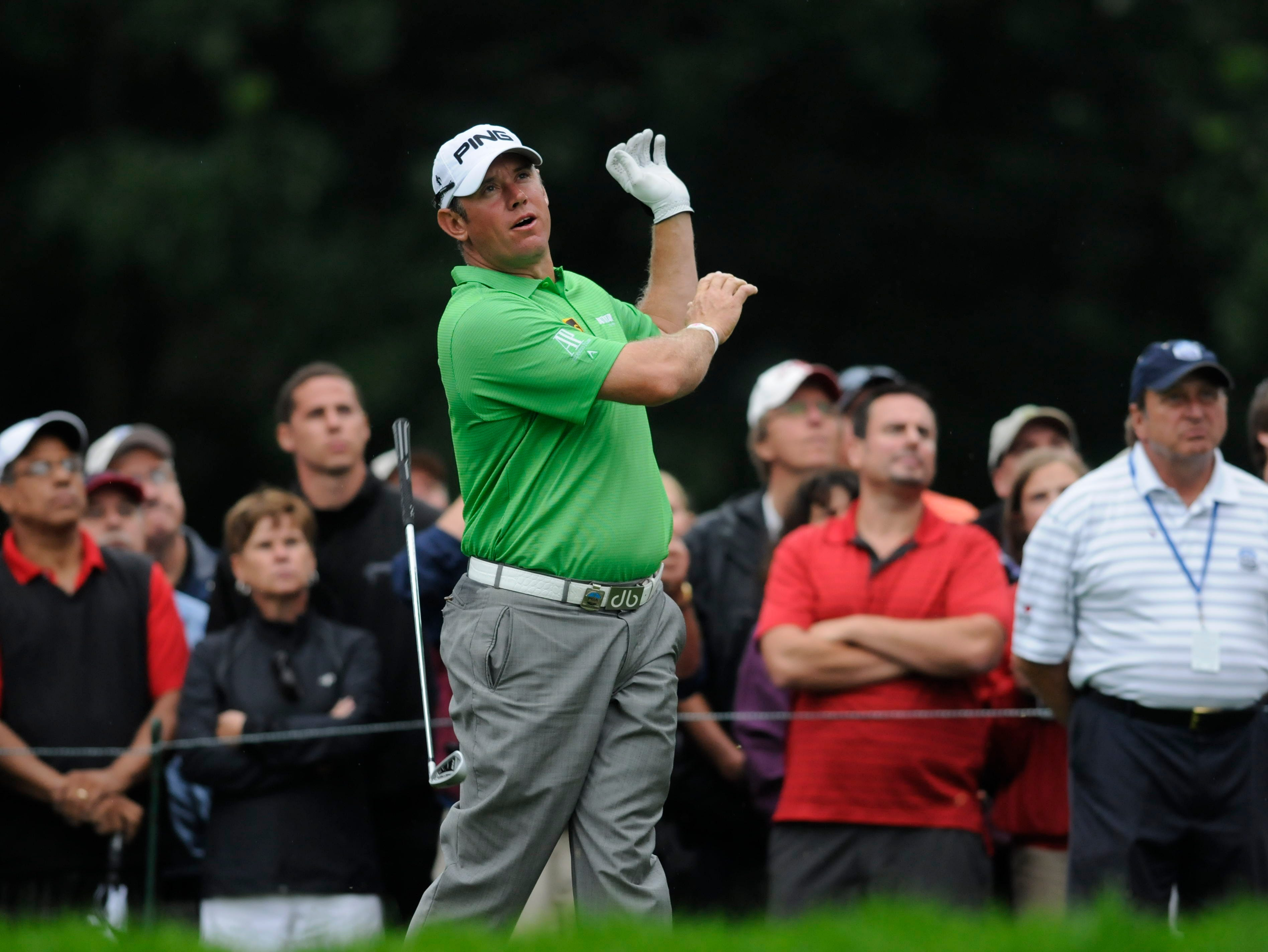 Lee Westwood drops his club after his tee shot on the 13th hole.