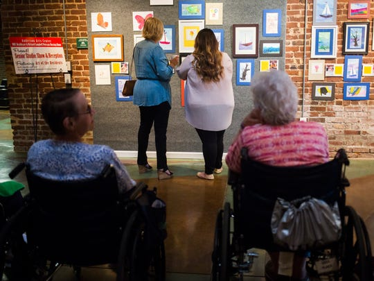 People admire the artwork an art exhibit of original watercolors created by local senior citizens through a program called Senior Studio on Tuesday, September 27, 2016 at the Anderson Arts Center.